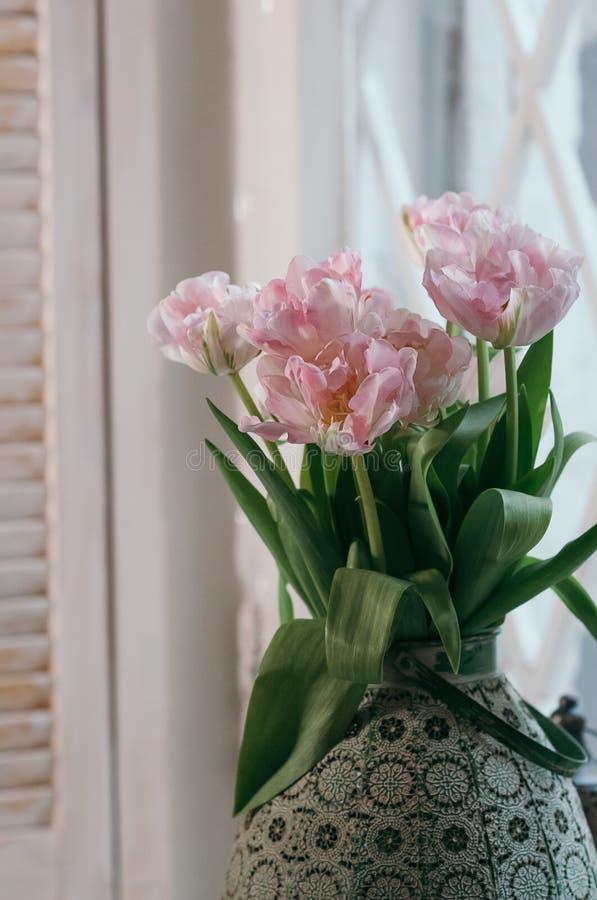 Um delicado centrou-se o ramalhete de tulipas cor-de-rosa em um vaso velho grande sobre uma vitória fotos de stock royalty free