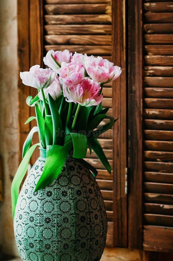 Um delicado focalizou o ramalhete das flores em um vaso velho imagens de stock