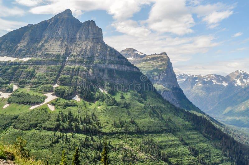 Um dente deu forma aos projetos da montanha altos acima do assoalho do vale no parque nacional de geleira imagens de stock royalty free
