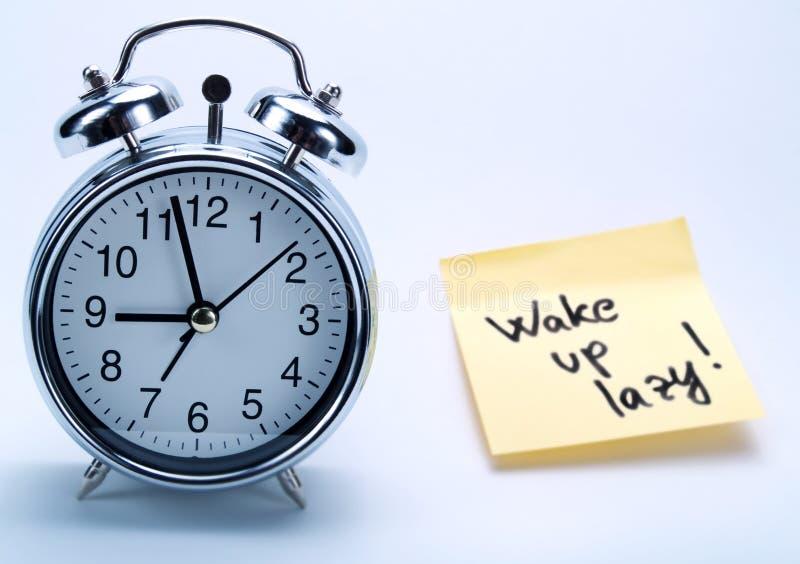 Um despertador e uma nota amarela foto de stock