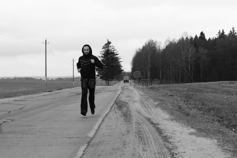 Um desportista está correndo em uma estrada foto de stock