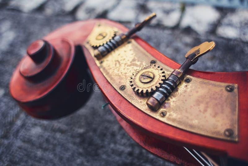 Um detalhe antigo do violoncelo dos detalhes do mogno e do bronze de Siz no fundo dos pavers velhos Parte de madeira de vagabundo fotografia de stock