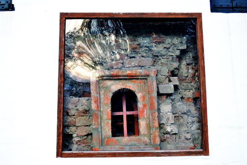 Um detalhe de parede velha com uma janela que mostre tijolos vermelhos imagem de stock