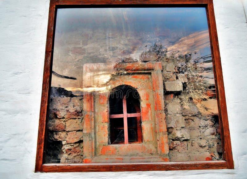 Um detalhe de parede velha com uma janela que mostre tijolos vermelhos fotografia de stock