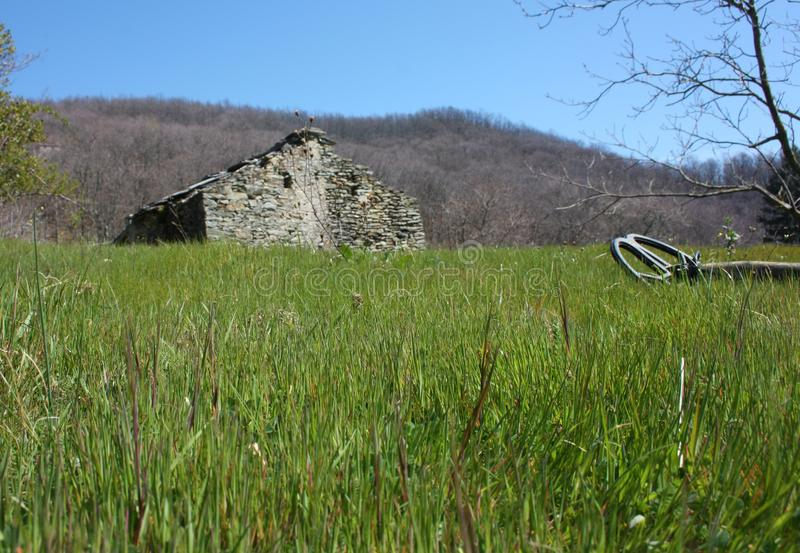 Um detector de metais que descansa em um gramado, encontrando-se muito em um esclarecimento do verde, um campo dos cumes de Apuan imagens de stock royalty free
