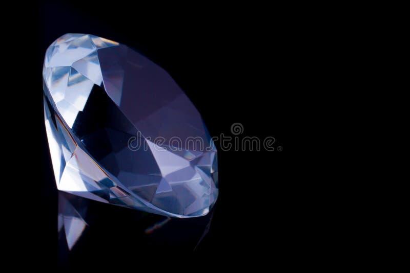 Um diamante enorme em uma superfície preta do espelho, uma reflexão de um diamante imagens de stock