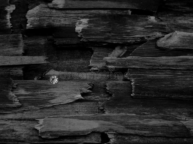 Um diamante entre partes de madeira quebradas fotos de stock