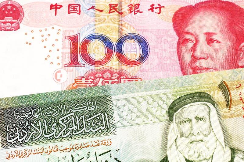 Um dinar um jordano com uma nota chinesa do yuan imagem de stock