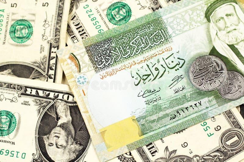 Um dinar um jordano em um fundo de notas de dólar do americano um imagem de stock