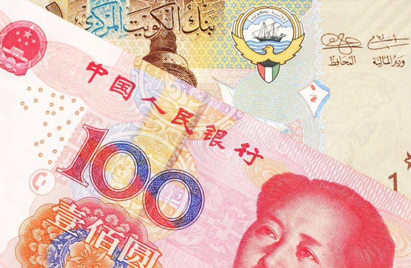 Um dinar kuwaitiano com um fim chinês da nota do yuan acima imagens de stock royalty free