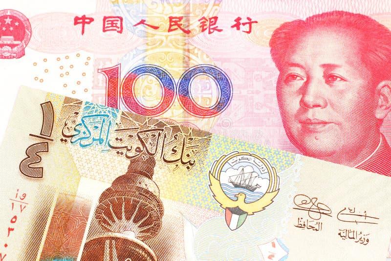 Um dinar kuwaitiano com um fim chinês da nota do yuan acima foto de stock