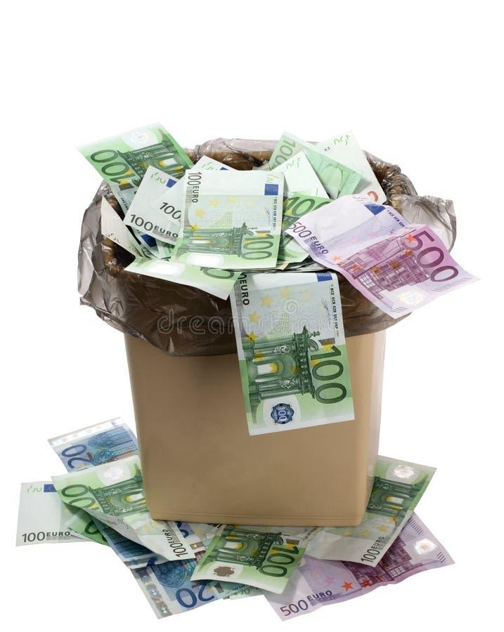 Um dinheiro está em uma cubeta do lixo. imagens de stock