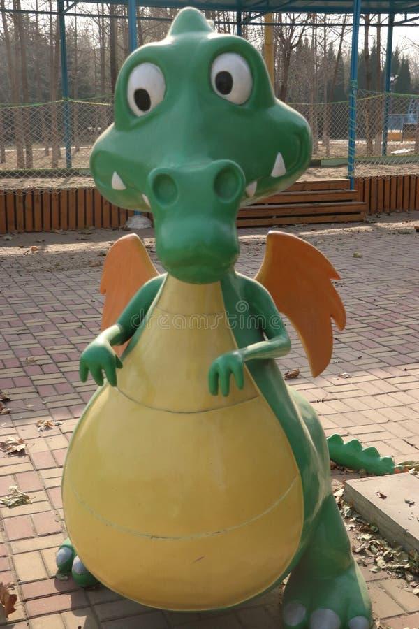 Um dinossauro dos desenhos animados no campo de jogos fotos de stock