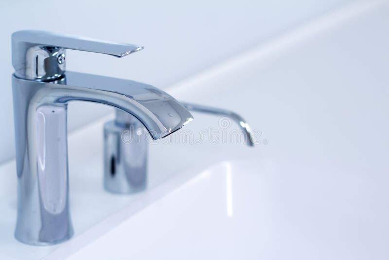 Um dissipador moderno da torneira de ?gua com o torneira no estilo minimalistic e o distribuidor incorporado do sab?o no banheiro imagem de stock royalty free