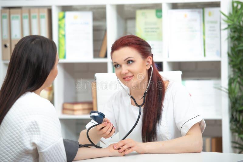 Um doutor amigável de sorriso toma um paciente em seu escritório e em medidas da pressão A mulher dá o conselho médico fotografia de stock royalty free