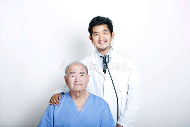 Um doutor asiático novo com sua mão no ombro de um paciente adulto superior fotos de stock