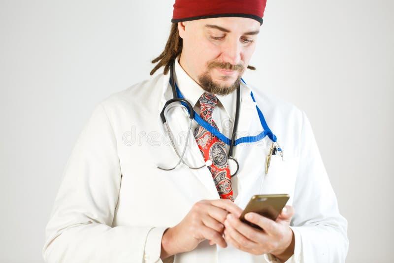 Um doutor com dreadlocks e uma barba está guardando um smartphone em suas mãos, um estetoscópio e um crachá está pendurando em to fotografia de stock royalty free
