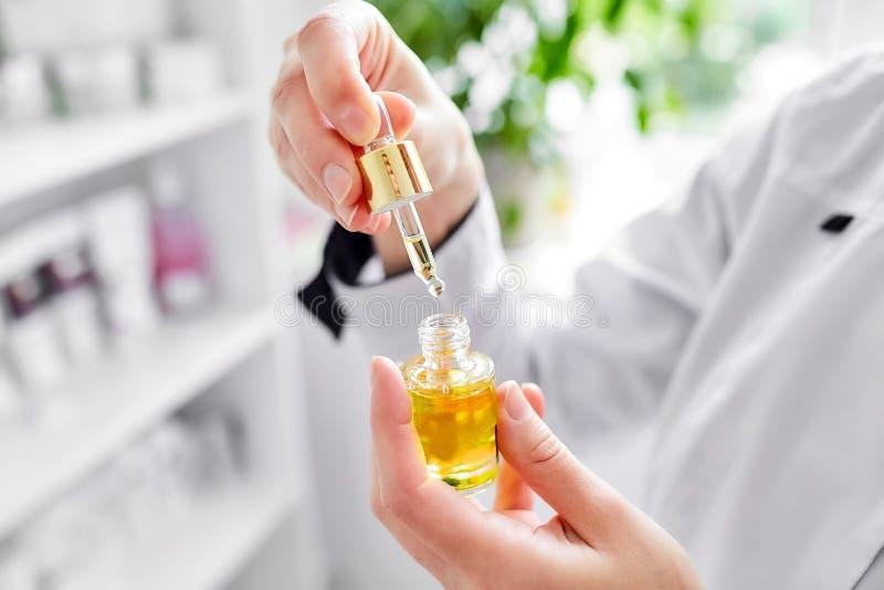 Um doutor-cosmetologist fêmea guarda uma garrafa do óleo do argão foto de stock