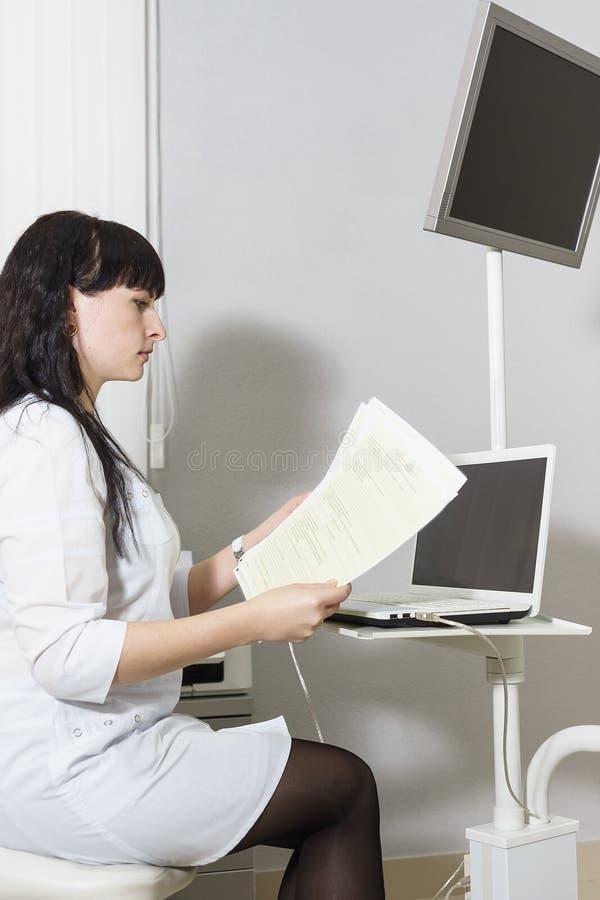 Um doutor de meia idade em um revestimento branco examina os resultados do exame do paciente Métodos do diagnóstico das doenças imagem de stock
