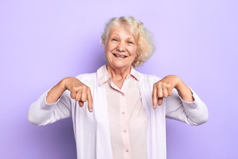 Um doutor fêmea da senhora feliz idosa que aponta para baixo em um espaço da cópia fotos de stock royalty free