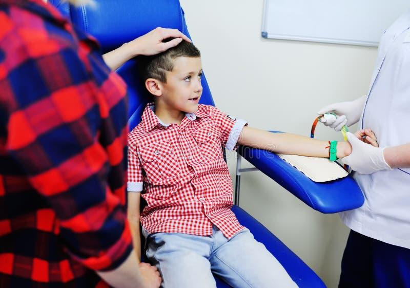 Um doutor ou uma enfermeira tomam o sangue de uma veia em uma criança de um menino fotografia de stock