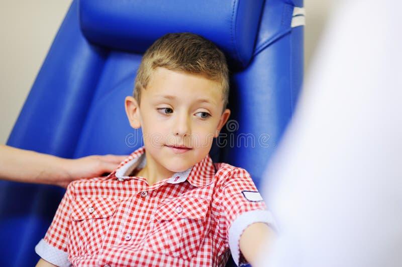 Um doutor ou uma enfermeira tomam o sangue de uma veia em uma criança de um menino fotos de stock