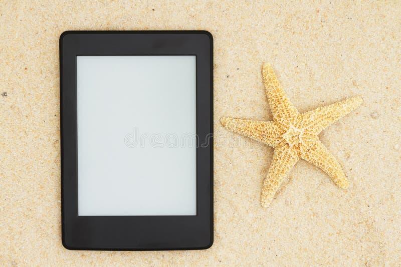 Um e-leitor na praia para sua leitura do verão imagem de stock