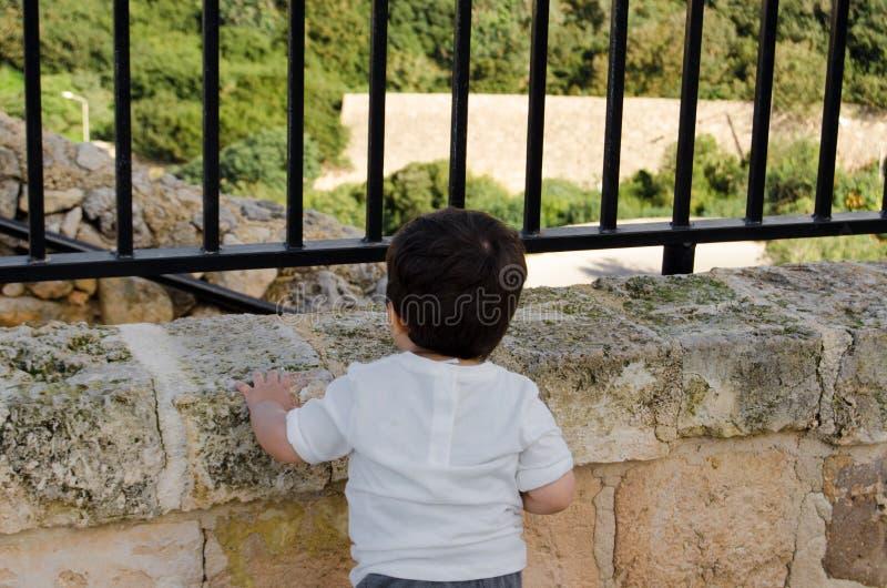 Um e um ner estando da meia criança dos anos de idade a parede e vista para baixo conceito da criança do loonley fotos de stock
