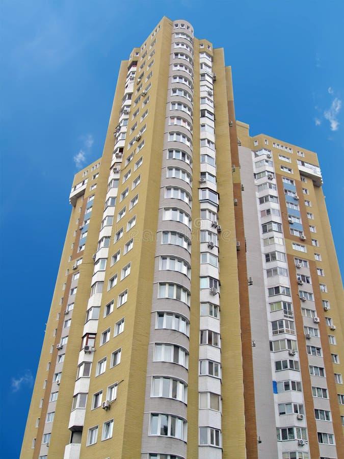Um edifício elevado urbano, tijolo amarelo, céu azul fotografia de stock