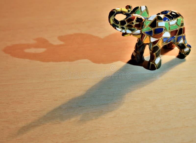Um elefante cerâmico colorido com suas sombras refletiu no assoalho fotografia de stock royalty free