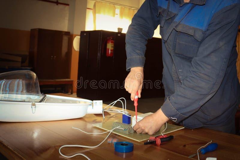 Um eletricista do homem que trabalha trabalhos, recolhe o circuito bonde de uma grande lâmpada de rua branca com fios, um relé em imagem de stock