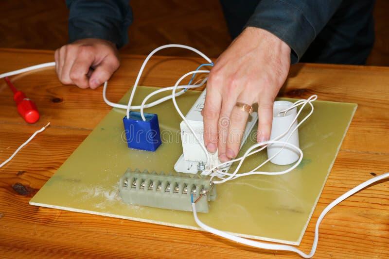 Um eletricista do homem que trabalha trabalhos, recolhe o circuito bonde de uma grande lâmpada de rua branca com fios, um relé em fotografia de stock