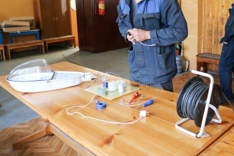 Um eletricista do homem que trabalha trabalhos, recolhe o circuito bonde de uma grande lâmpada de rua branca com fios, um relé em imagem de stock royalty free