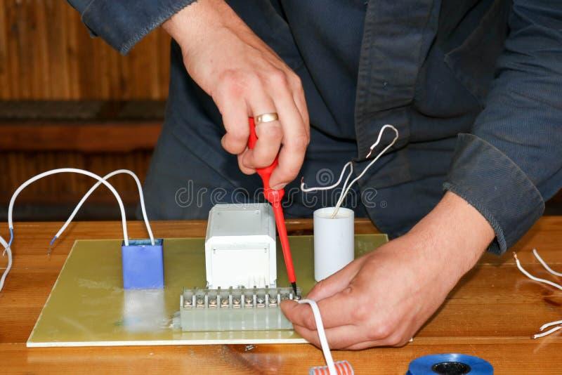 Um eletricista do homem que trabalha trabalhos, recolhe o circuito bonde de uma grande lâmpada de rua branca com fios, um relé em fotos de stock
