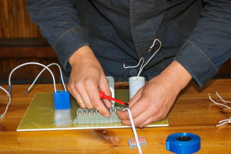 Um eletricista do homem que trabalha trabalhos, recolhe o circuito bonde de uma grande lâmpada de rua branca com fios, um relé em fotografia de stock royalty free