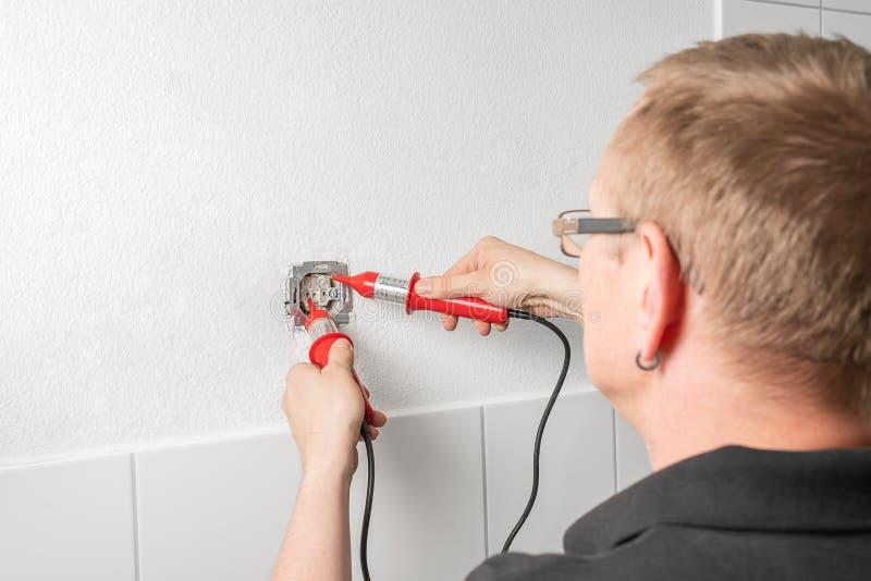 Um eletricista mede a tensão em uma tomada de poder com um indicador da tensão imagens de stock