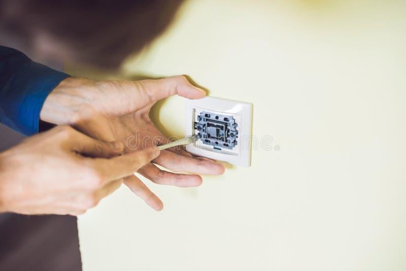Um eletricista novo que instala um interruptor bonde em um hou novo fotografia de stock royalty free