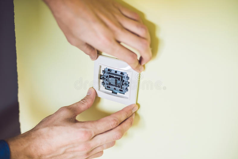 Um eletricista novo que instala um interruptor bonde em um hou novo foto de stock royalty free