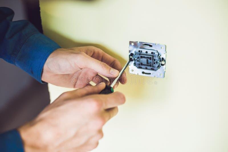 Um eletricista novo que instala um interruptor bonde em um hou novo fotos de stock royalty free