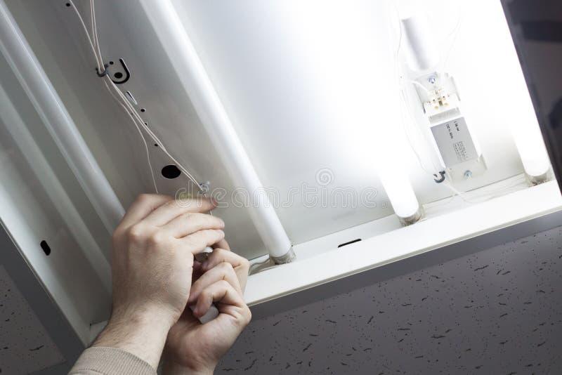 Um eletricista veio ao escritório verificar e reparar a luz imagem de stock royalty free