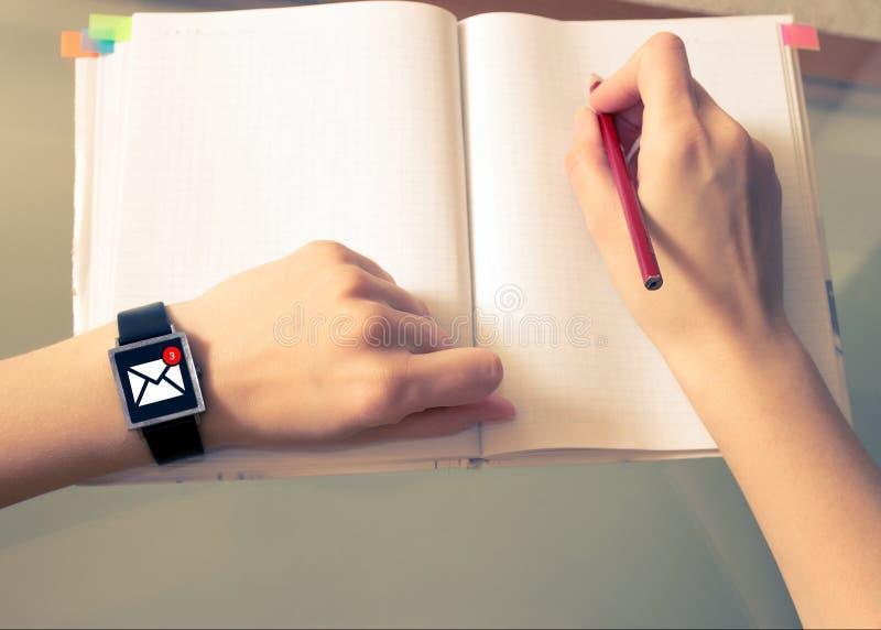 Um email em linha em um relógio esperto Um pulso de disparo esperto em uma mão do ` s da mulher Ícone em linha da mensagem foto de stock