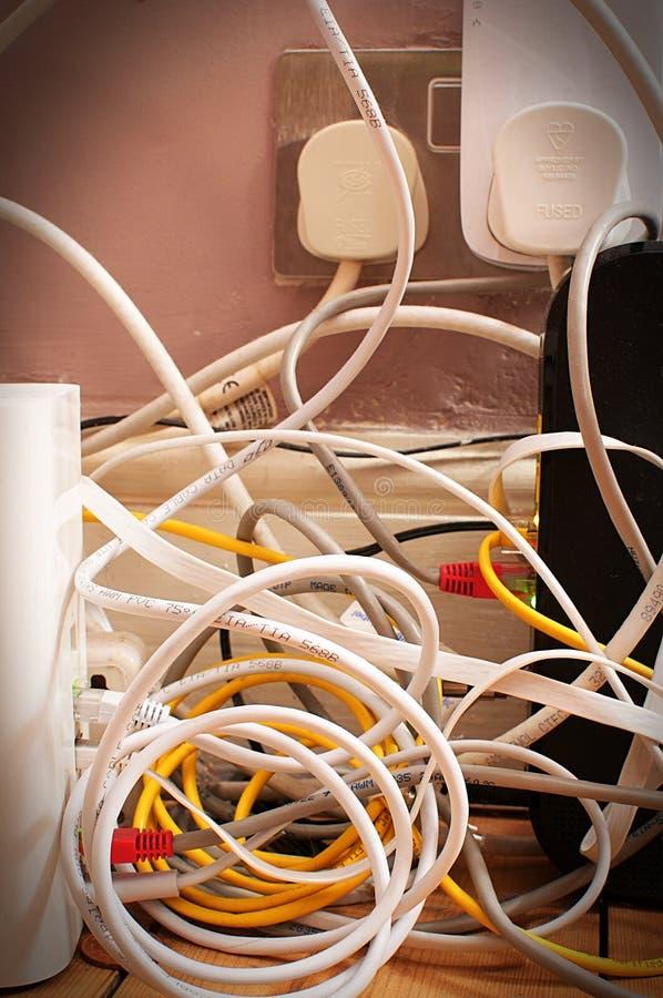 Um emaranhado dos fios ao lado de um soquete da tomada imagens de stock royalty free