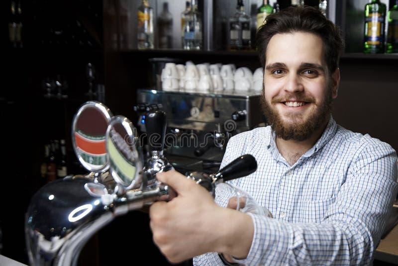 Um empregado de bar farpado com um sorriso derrama a cerveja foto de stock royalty free