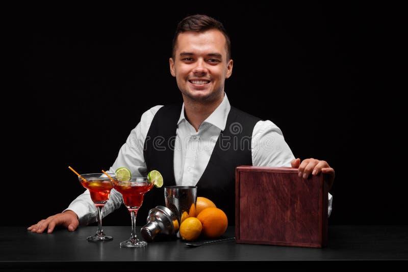 Um empregado de bar que veste um terno clássico atrás de um contador da barra em um fundo preto Muitos ingredientes coloridos em  imagens de stock