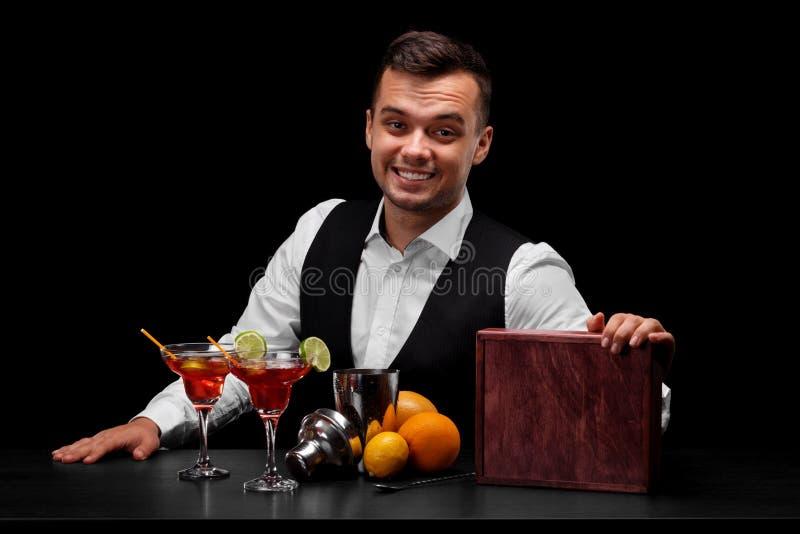 Um empregado de bar que veste um terno clássico atrás de um contador da barra em um fundo preto Muitos ingredientes coloridos em  foto de stock