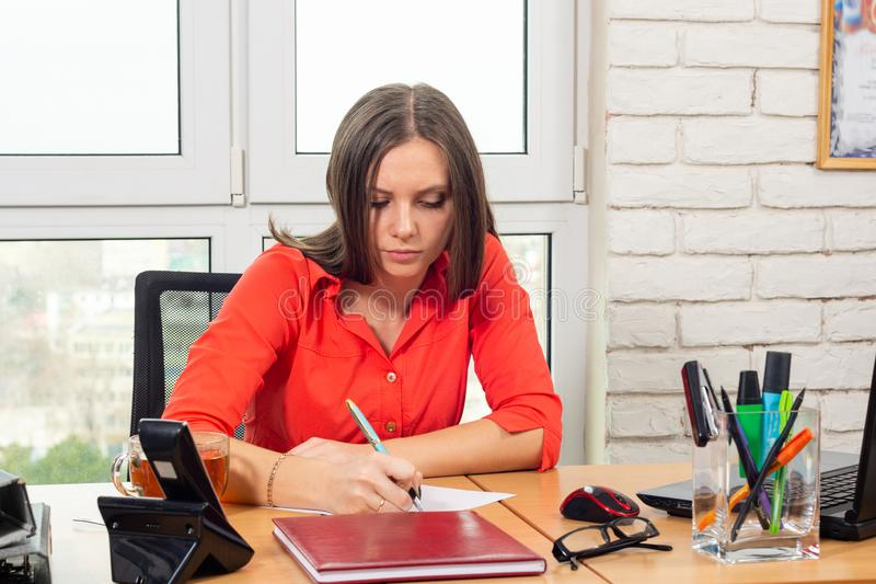 Um empregado redige uma indicação na mesa no escritório imagem de stock