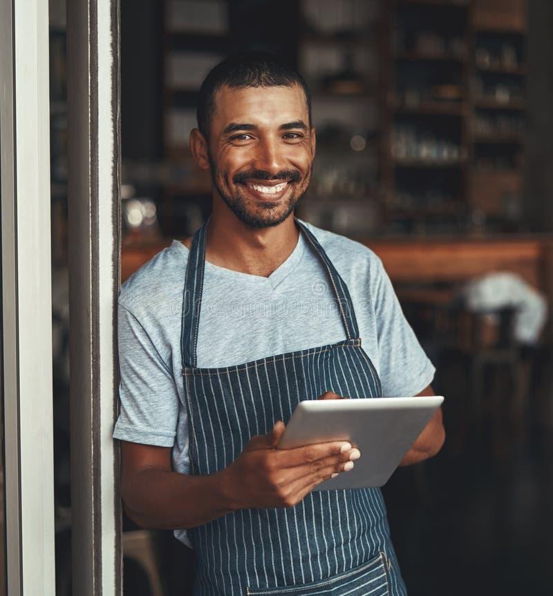 Um empresário africano novo do café que guarda a tabuleta digital fotografia de stock