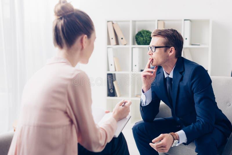 Um empresário bonito e repressivo está olhando para o outro lado enquanto dá entrevista ao jornalista Pensive, um empresário b imagens de stock royalty free