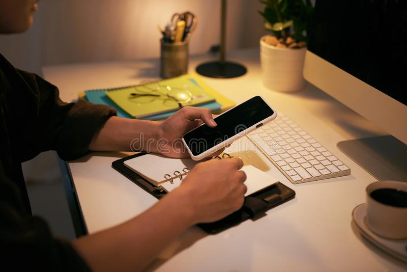 Um empresário está checando o telefone e escrevendo em seu caderno enquanto está sentado na mesa de trabalho fotos de stock