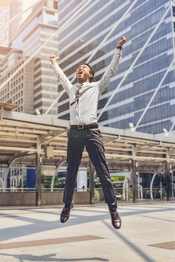 Um empresário masculino asiático está saltando de seu sucesso no busine fotografia de stock royalty free